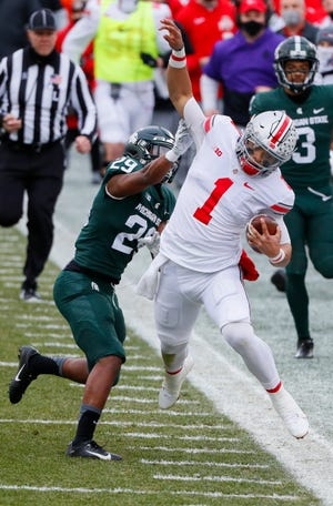Ohio State quarterback Justin Fields pushes off Michigan State cornerback Shakur Brown on a run during the first quarter.