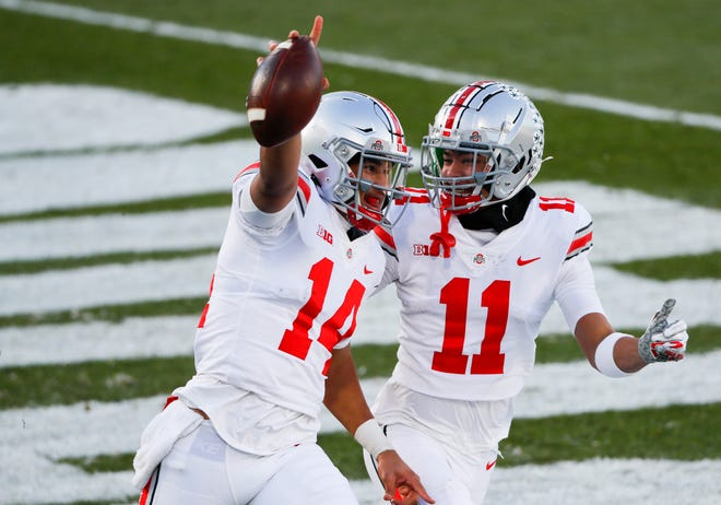 Ohio State quarterback C.J. Stroud (14) celebrates with wide receiver Jaxon Smith-Njigba after scoring a rushing touchdown during the fourth quarter of the Buckeyes' win at Michigan State.