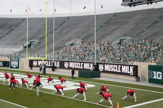 Ohio State players stretch in the south end zone before Saturday's game at Spartan Stadium.