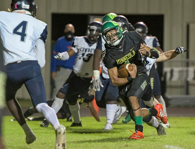 Lake Minneola quarterback Robbie Sanders (1) dodges tacklers on his way to a touchdown in Friday's Class 6A-Region 2 championship game against Tampa Gaither in Minneola. [PAUL RYAN / CORRESPONDENT]