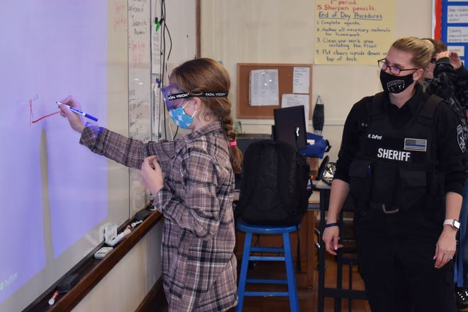 Poland Central School District sixth-grader Lia Dutcher tries to write her name on a line while wearing goggles designed to simulate alcohol impairment, as Herkimer County Sheriff's Office Deputy Heather DuPont, the Poland Central School District safety patrol officer, looks on.
