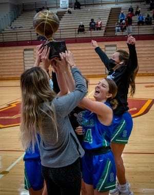 Blue Springs South senior Rebekah Hardin (24) and the Jaguars hoist the championship trophy after defeating North Kansas City 53-37 Friday to claim their second straight Winnetonka Tournament title Friday.