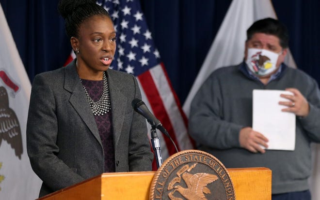 Illinois Department of Public Health Director Ngozi Ezike, with Gov. J.B. Pritzker in the background, gives a coronavirus update from the Thompson Center in downtown Chicago on Tuesday, Dec. 1, 2020.
