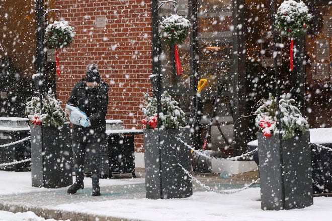 A worker pours ice melting pellets on the walkway outside a restaurant, Saturday, Dec. 5, 2020, in downtown Marlborough.
