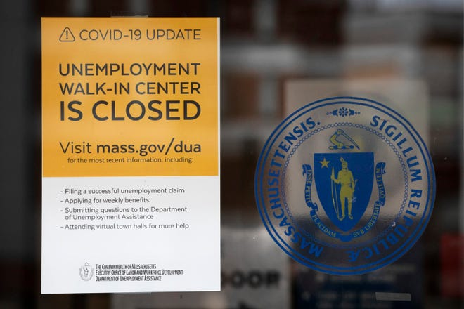 A sign announces the closure of the Massachusetts Unemployment Office, Saturday, May 9, 2020, in Boston.