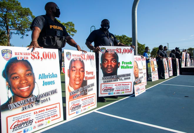 Photos of 25 people killed in Riviera Beach form the background for a succession of speakers decrying gun deaths on Saturday, Dec. 5, 2020.