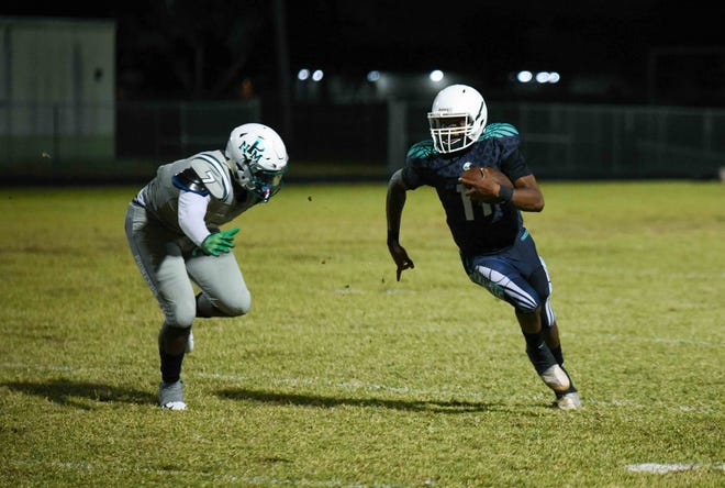 Atlantic quarterback Guenson Alexis (11) carries the ball while North Miami middle linebacker Amahri McCray (7) approaches during the second half of Friday's Class 7A gold bracket quarterfinal game in Delray Beach.