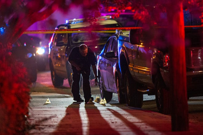 An investigator photographs evidence markers as West Palm Beach police investigate the shooting of two security officers outside Rain Gentlemen's Club at Old Okeechobee Rd. and Wilkins Avenue before dawn Thursday, Oct. 29, 2020. Police say the security officers were transported to the hospital with non-life threatening injuries.