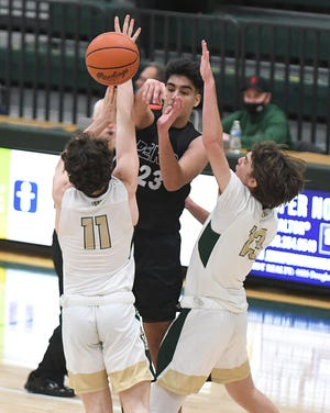 Haythem Hmeidan of Perry dishes off the ball with double coverage from Jack Davis (11) and Alec Marran (13) of GlenOak  in the last minutes of their matchup at GlenOak.