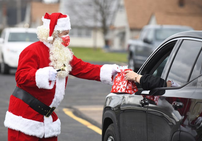 Doug Houtz , a member of Plumbers and Pipefitters Local 94, passes out presents to union retirees at a drive-thru Christmas party held at their training center in Canton.