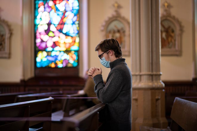 A man wearing a face mask kneels to pray during the noon Mass at the Cathedral of St. Paul on Thursday in Worcester.