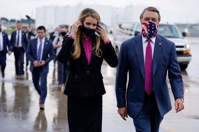 In this July 15 file photo Sen. Kelly Loeffler, R-Ga., puts on a face mask as she walks with Sen. David Perdue, R-Ga., right, at UPS Hapeville Airport Hub in Atlanta.