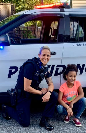 Kirsten Doldoorian takes a break from her job as a member of the Providence Police Department to have her photo taken with a young girl from the Cranston Street neighborhood who aspires to be an officer one day.