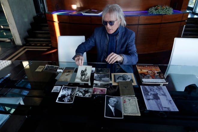 Jed Leiber shows photos of his grandfather Saemy Rosenberg's life at home Thursday in Los Angeles.