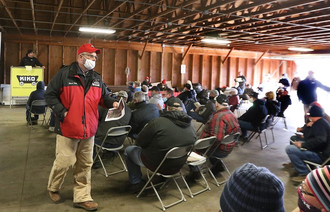 Matt Kiko of Kiko Auctions works during the Oak Shadows Golf Club auction held Saturday in the cart barn. (TimesReporter.com / Jim Cummings)