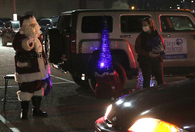 Santa Claus waves at children in the cars as they pass by during the New Philadelphia  reverse Christmas Parade in the New Towne Mall parking lot Friday.