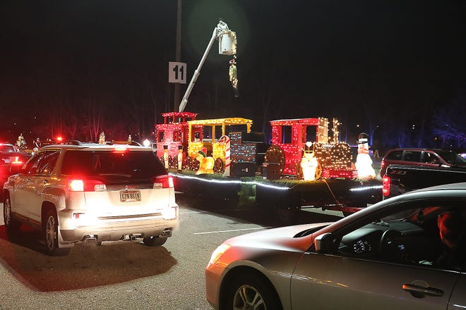Cars pass by floats during the New Philadelphia  reverse Christmas Parade in the New Towne Mall parking lot Friday.
