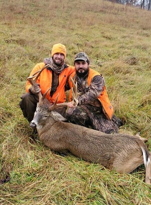 Lance Taylor (left) and Jake Fawcett show off the deer that Taylor harvested on opening day of gun season.