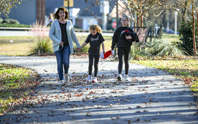 Ashley Melton, left, Sadie Fowler, and Paisley Melton of Belton walk along the Rail Trail on their way to the Belton Christmas Parade Saturday, December 5, 2020.