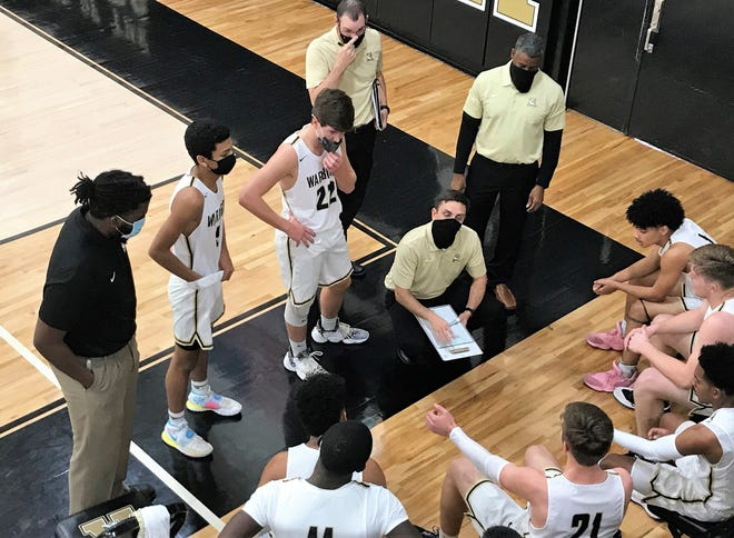Abilene High coach Justin Reese, squatting, talks to his players during a first-half time-out Friday at Eagle Gym. The Eagles trailed just once against Peaster but had to battle to a 57-50 nondistrict win.