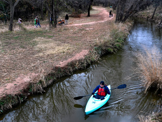 Mitch Barnett paddles Cedar Creek in a kayak as others walk along the nearby trail during the Mayor's Hike on  Saturday. Barnett made it about halfway through the route before turning back.