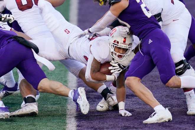 Stanford running back Austin Jones dives into the end zone for a three-yard touchdown run against Washington in the first half Saturday at Husky Stadium. The Cardinal dominated the line of scrimmage in the first half, putting the Huskies in a hole, 21-3, for the second straight week. UW's offense woke up in the third quarter with rushing touchdowns from Sean McGrew and Dylan Morris, but the Huskies trailed 31-26 late in the fourth quarter.   The game finished after the Sun's print deadline, see coverage on www.kitsapsun.com and in Monday's print edition.