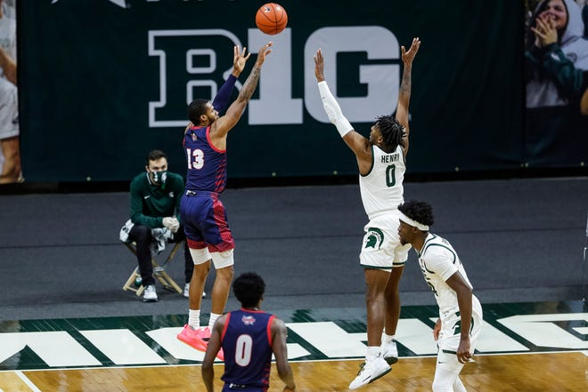 Detroit Mercy guard Matt Johnson shoots against Michigan State forward Aaron Henry during the first half at Breslin Center in East Lansing on Dec. 4, 2020.