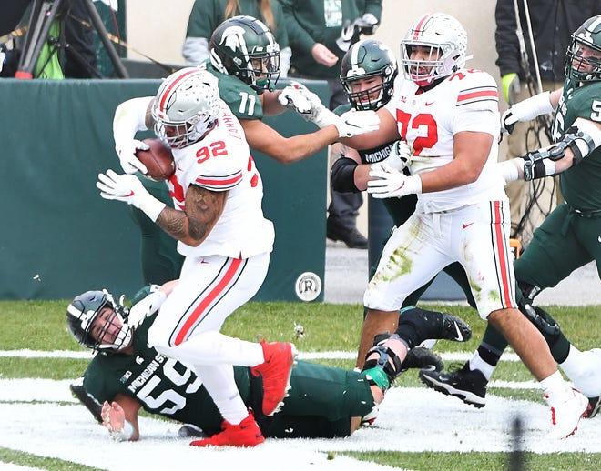 Pemain Ohio State Haskell Garrett menarik bola yang ia berikan kepada quarterback Michigan State Rocky Lombardi di zona akhir untuk touchdown untuk Ohio State pada kuarter kedua.