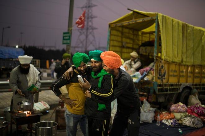 Petani India melihat ponsel di lokasi protes terhadap undang-undang pertanian baru di perbatasan negara bagian Delhi-Uttar Pradesh, India, Sabtu, 5 Desember 2020.