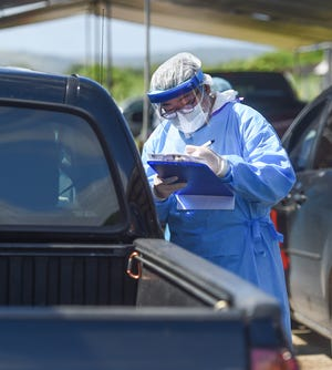 A University of Guam nursing student screens a patient at community COVID-19 testing drive-thru in Tiyan, Dec. 5, 2020.