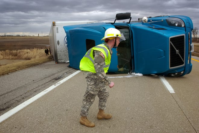 An emergency worker struggles against the wind at the scene of an overturned semi-tractor trailer in 2020. Montana meteorologists are forecasting gusts of up to 70-mph along the Interstate 15 corridor over the next 48 hours.