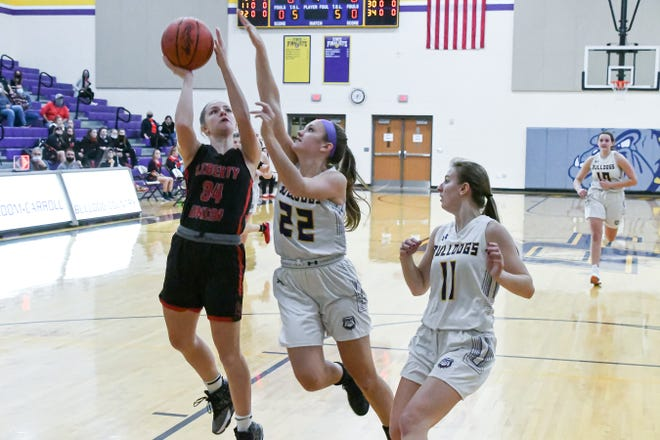 Liberty Union senior Emilee Powers shoots the ball as Bloom Carroll senior McKenzie Powers attempts to block her shot. BC prevailed 45-40.