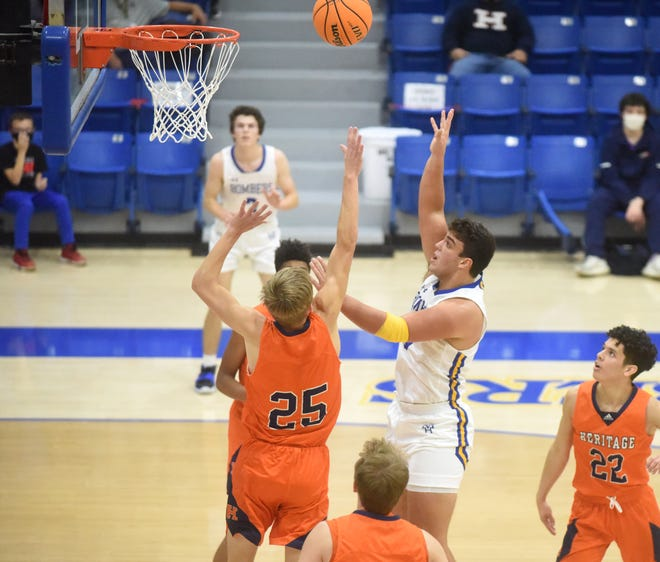 Mountain Home's Dawson Tabor puts up a shot against Rogers Heritage on Friday night at The Hangar.