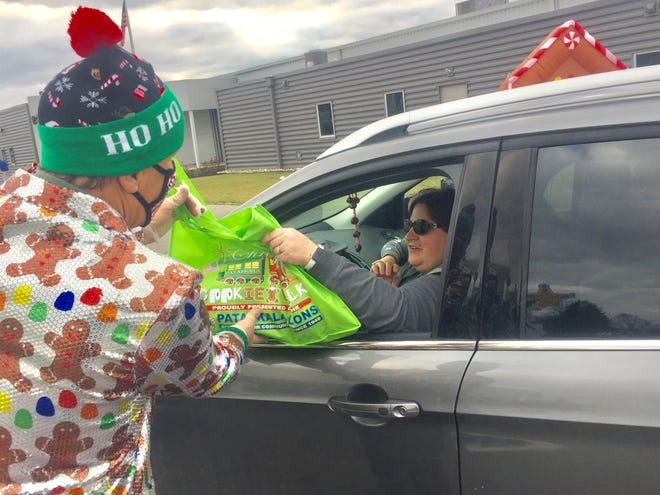 Fred Biesecker hands a bag of cookies to one of the first of hundreds of cars to pass through the Pataskala Lions Club Christmas drive-through event.