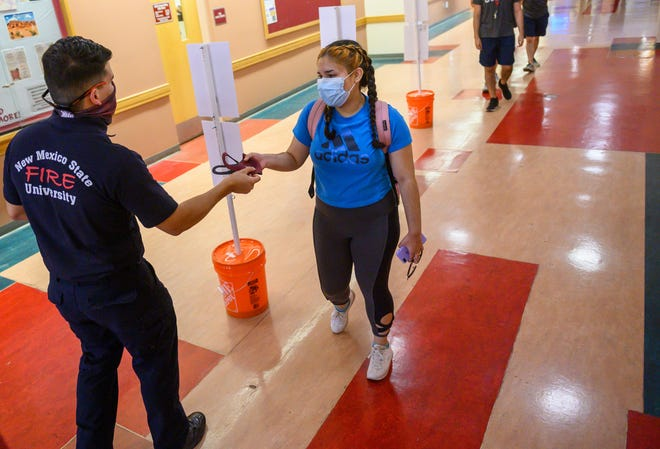 A firefighter with the New Mexico State University Fire Department distributes face masks to people on the NMSU campus in August. Women, racial minorities and older adults were more likely to wear face masks as a protective measure to slow the spread of COVID-19, according to a new study co-authored by an NMSU researcher.