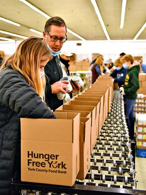 Volunteers work to pack holiday food boxes for the annual Give-A-Meal program during a family volunteering day at York County Food Bank's Emergency Food Hub on Haines Road in Springettsbury Township, Saturday, Dec. 5, 2020. Age limit restrictions were lifted for the day to allow younger children to experience being able to give back to those in need. Dawn J. Sagert photo