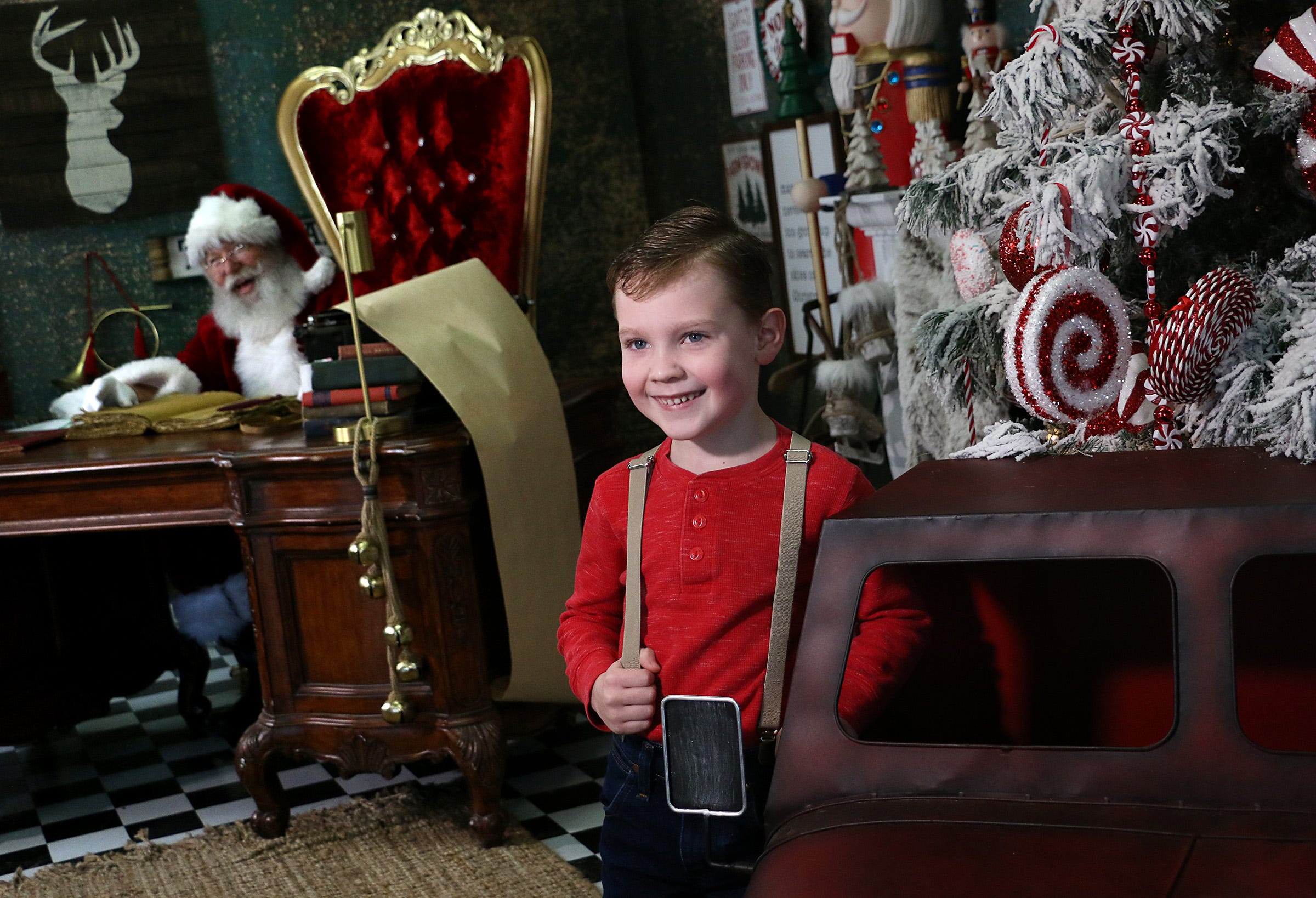 6 year old William Hopper poses for a portrait near Santa while visiting the Santa Experience with GMH Photography in Reno on Dec. 5, 2020.
