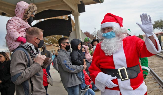 Bliss Bignall, right dressed as Santa Claus, waves to kids after arriving by train at the Railway Museum of San Angelo on Saturday, Dec. 5, 2020.