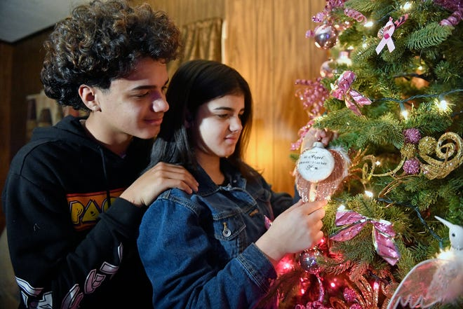 """Angel and Shyalyn Rivera place a special Christmas ornament on their tree. The ornament reads """"I have an Angel in Heaven - I call her Mom."""""""