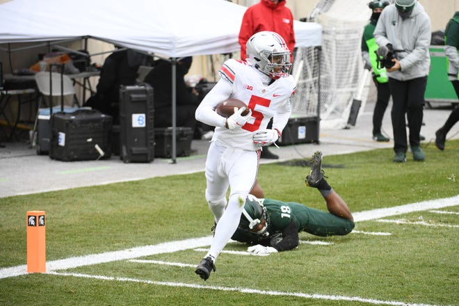 Ohio State wide receiver Garrett Wilson (5) gets past Michigan State cornerback Kalon Gervin for a touchdown during their game Spartan Stadium.
