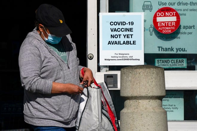 A customer walks past a sign indicating that a COVID-19 vaccine is not yet available at Walgreens in Long Beach, California.