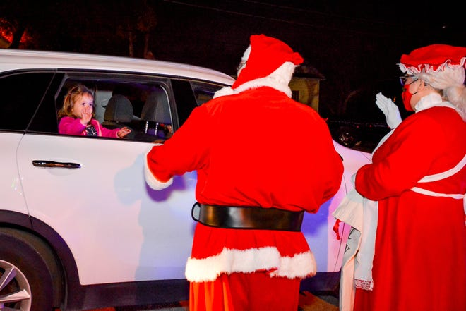 Mr. and Mrs. Claus greet Pflugerville residents downtown on Friday night during the Pfestival of Lights. The drive-thru event included lights and decorations, carolers and goodie bags for each vehicle.
