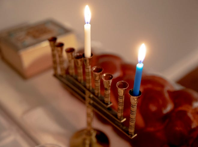 The first candle of the menorah remains lit during an annual Hanukkah dinner party last year. This year, Hanukkah will be celebrated with the people in your household and virtually with the community.