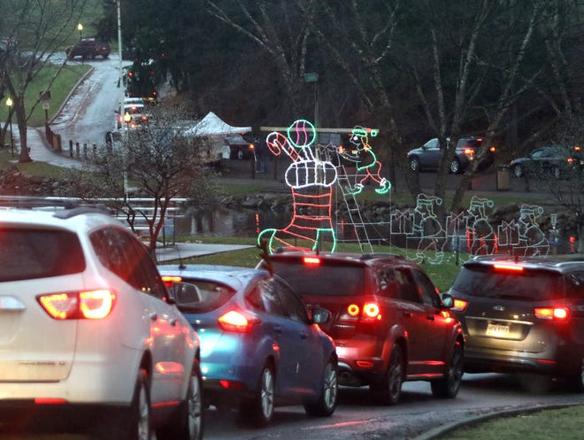 Cars snake their way Saturday night past Christmas lights near the pond, heading up the hill at Silver Park during a drive-thru holiday kickoff event in Alliance..