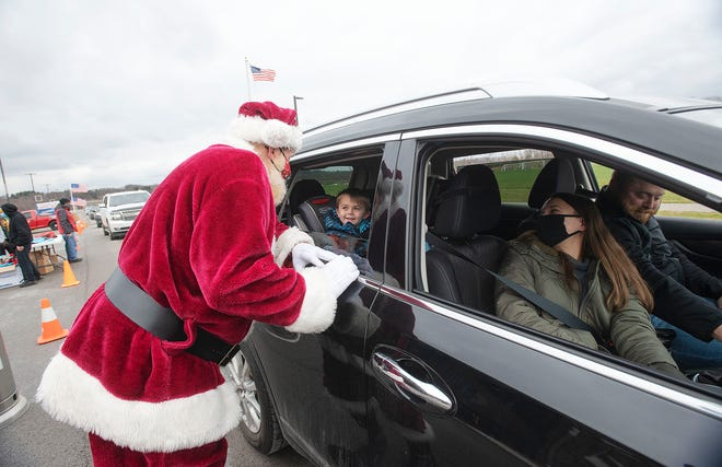"Santa hands out gifts to children at the ""Christmas in Chippewa"" drive-through event Saturday at Wright Fields, where more than 350 gifts, cookies and treats were distributed. The event was sponsored by the Chippewa Township Recreation Board."