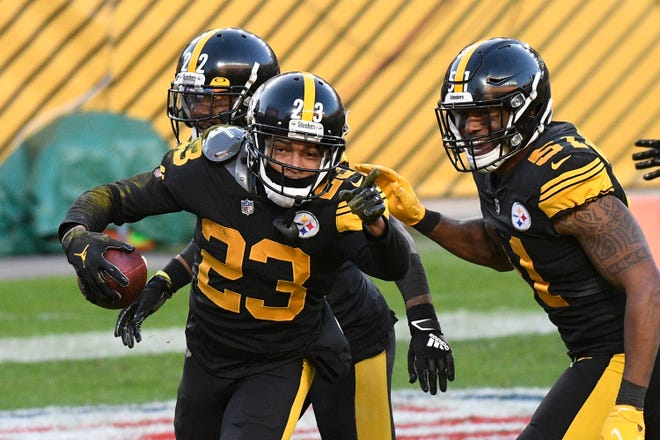 Pittsburgh Steelers cornerback Joe Haden celebrates with teammates in the end zone after intercepting a pass for a touchdown against the Ravens.