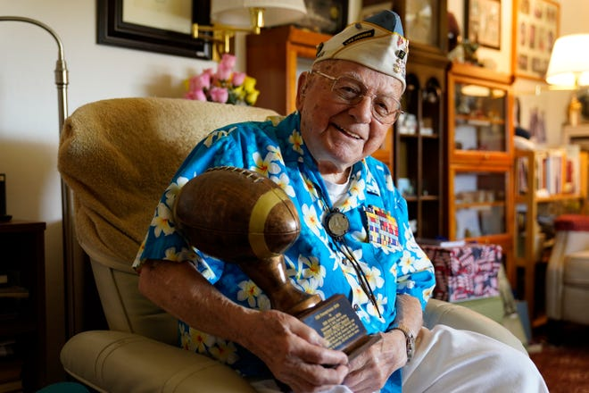 Mickey Ganitch, a 101-year-old survivor of the attack on Pearl Harbor, holds a football statue he was given, in the living room of his home Nov. 20 in San Leandro, Calif.