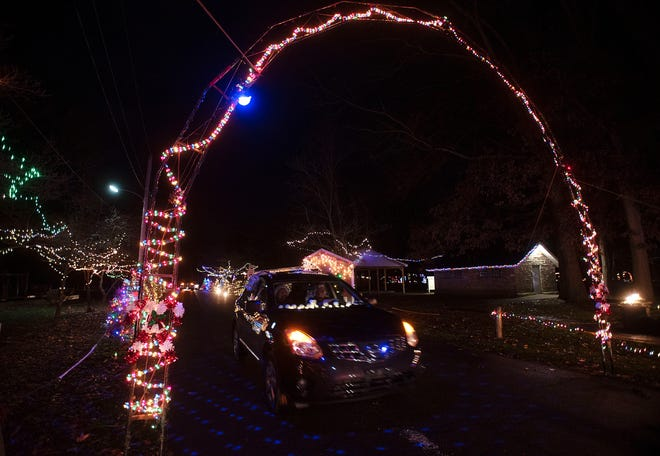 """A vehicle passes under a lighted arch that is part of the Ewing Park Christmas light display in Ellwood City. The COVID pandemic stopped the borough's annual Christmas parade, but an alternative event to usher in the holiday season was offered. With the Ellwood City police leading the way, residents in decorated vehicles were invited to follow in the """"Reindeer Caravan."""" Many also took a cruise through the park for the light display."""