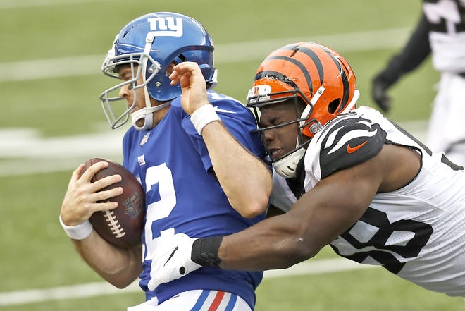 New York Giants quarterback Colt McCoy (12) is tackled by Cincinnati Bengals defensive end Carl Lawson during the second half of a Nov. 29 game in Cincinnati. McCoy is expected to start in place of the injured Daniel Jones this week.