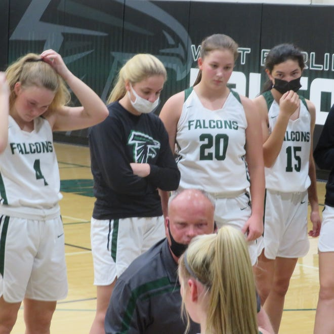 West Burlington High School girls basketball coach John Vandenberg talks to his team during a timeout in Saturday's victory over Mount Pleasant. Vandenberg's daughter, Natalie (4) is at left.